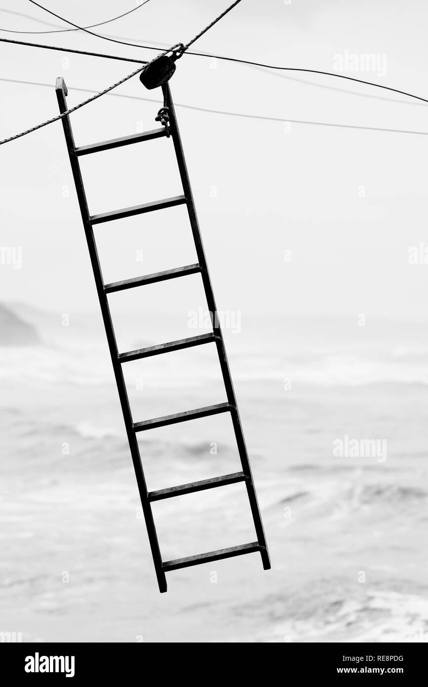 Ladder hanging from cables on the void - Stock Image