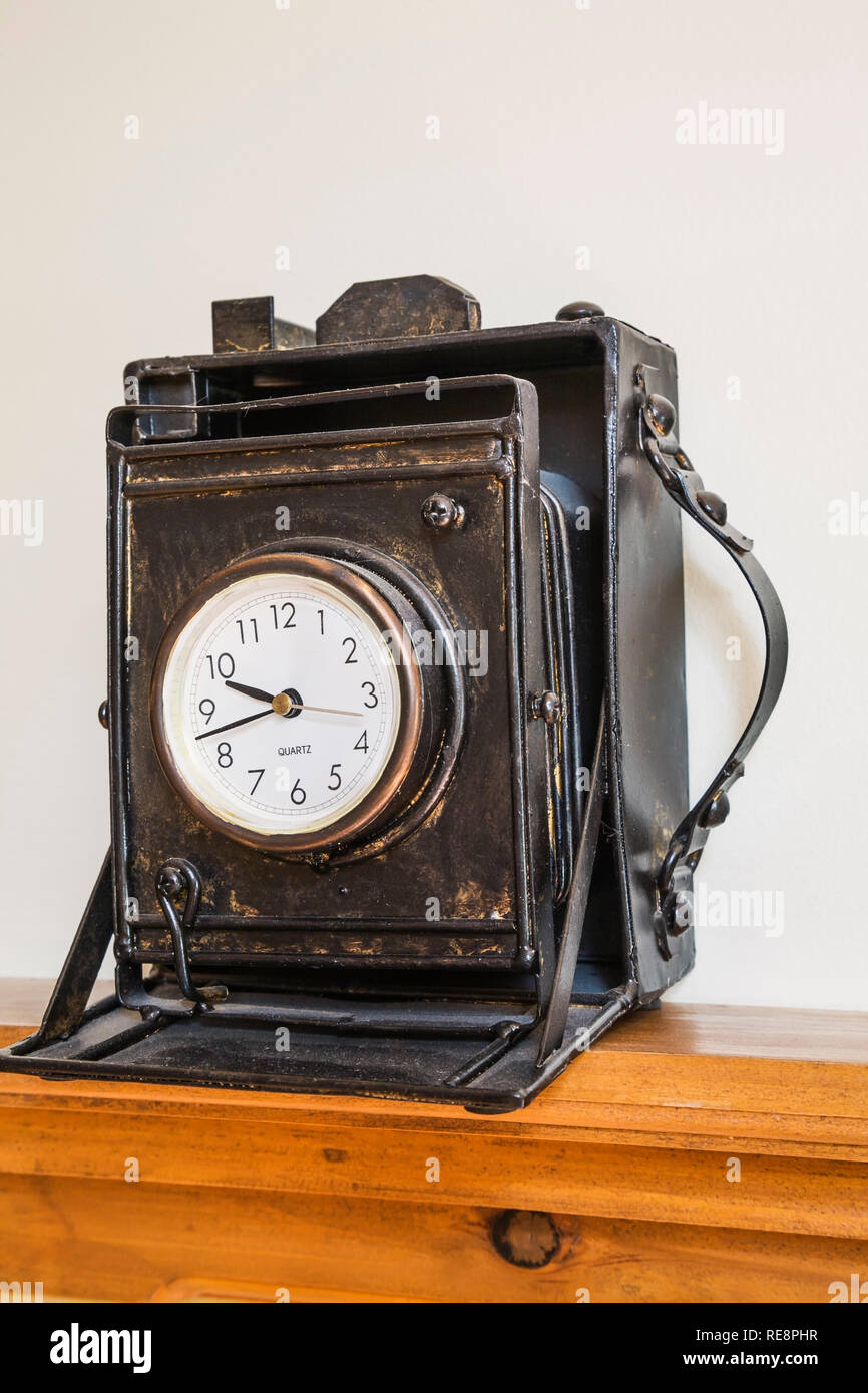 Black leather antique clock disguised as a camera with bellows on wooden shelf in home office on upstairs floor inside an old 1892 Canadiana home - Stock Image