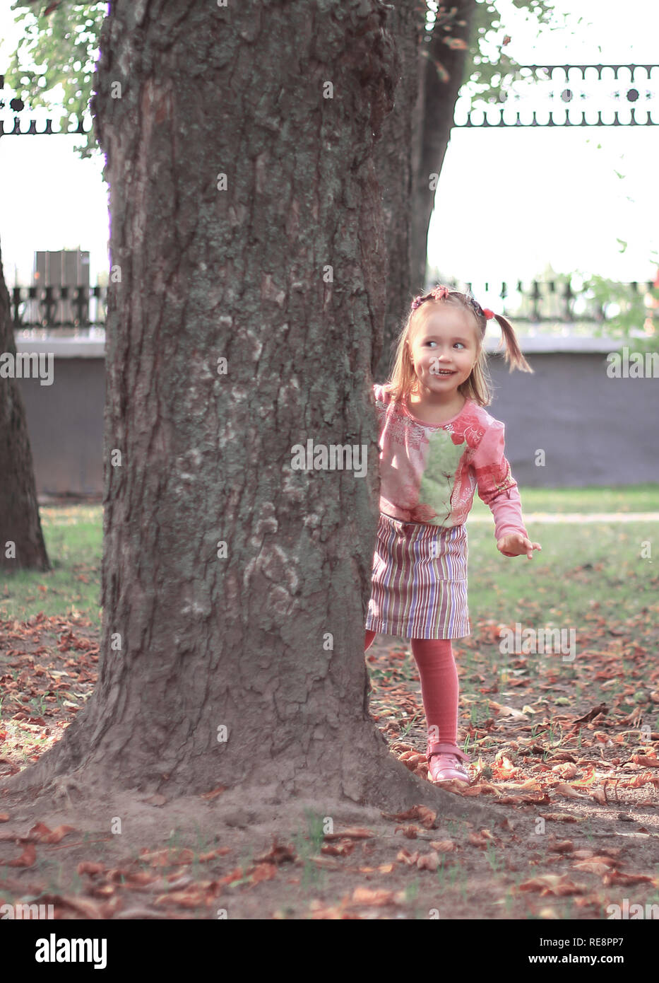 happy little girl playing hide and seek in the city Park - Stock Image