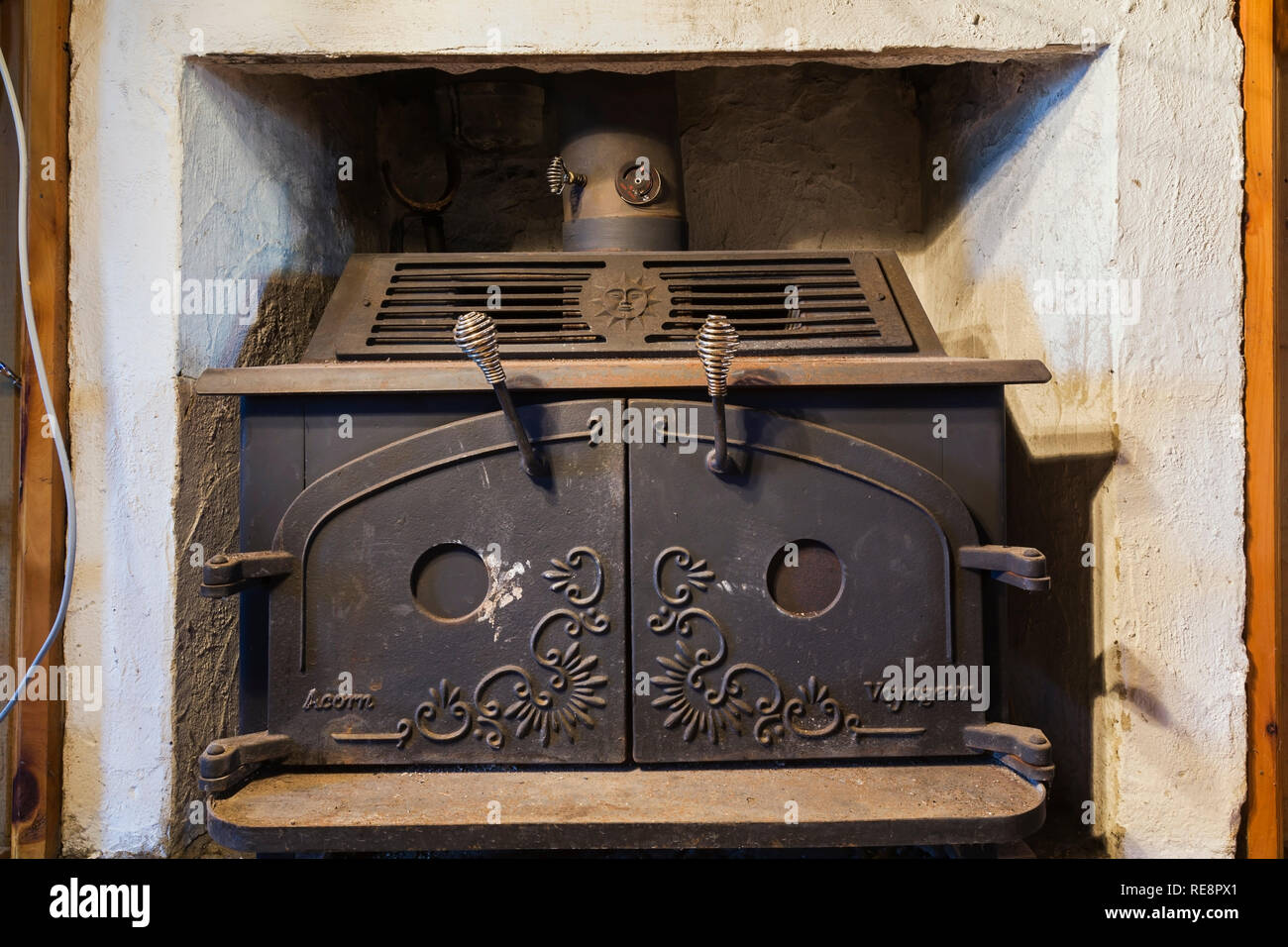Black cast iron Acorn Voyageur wood burning stove installed in fireplace inside an old 1807 Canadiana style home - Stock Image
