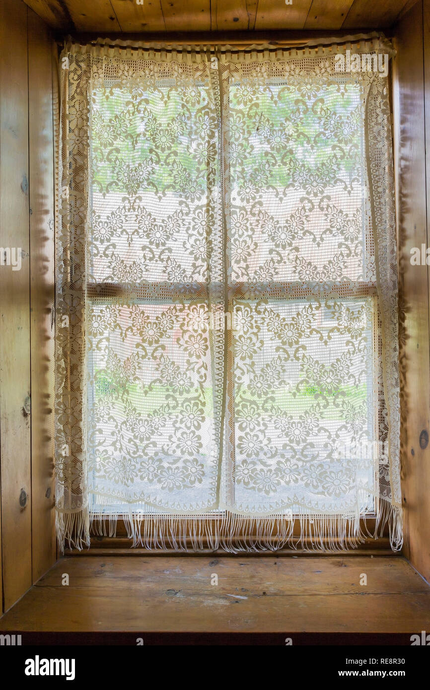 Recessed window with white lace curtains inside an old 1807 Canadiana style home - Stock Image