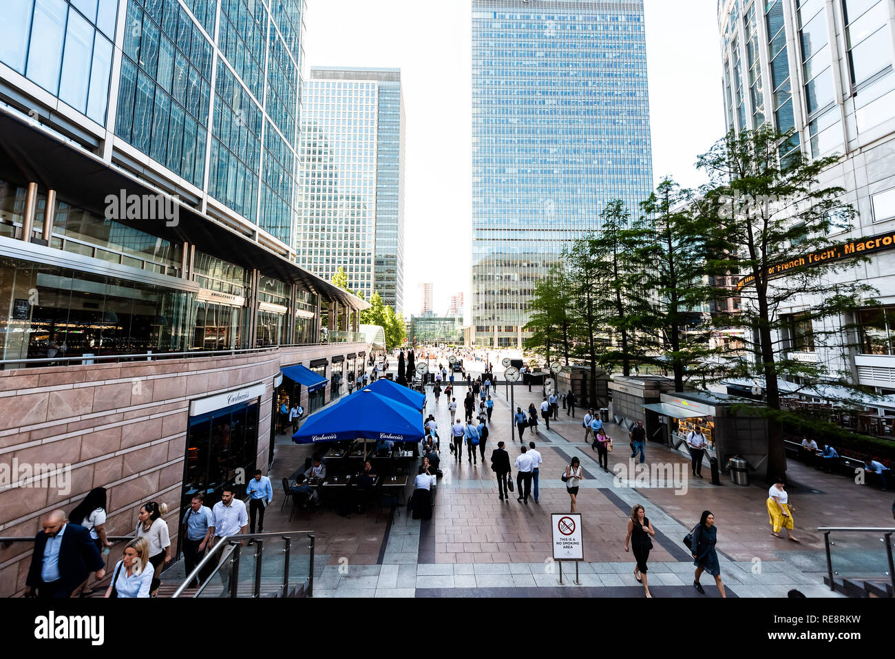 London, UK - June 26, 2018: People crowd commuters outside during morning commute rush hour in Canary Wharf Docklands with modern architecture clocks  - Stock Image