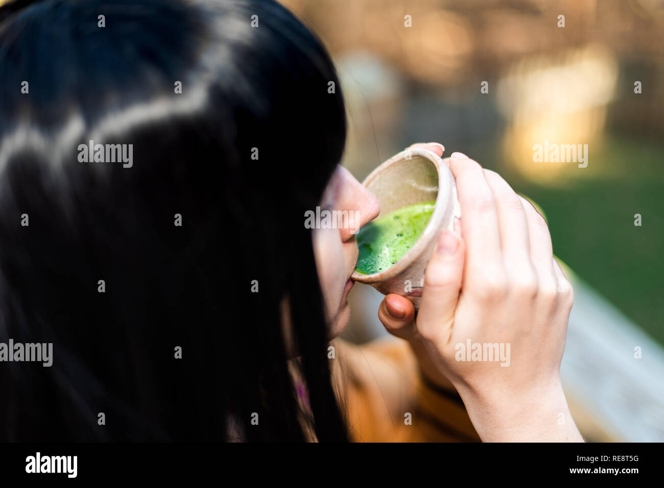 Woman holding tea cup face closeup drinking outside in backyard garden with girl and green matcha black hair Stock Photo