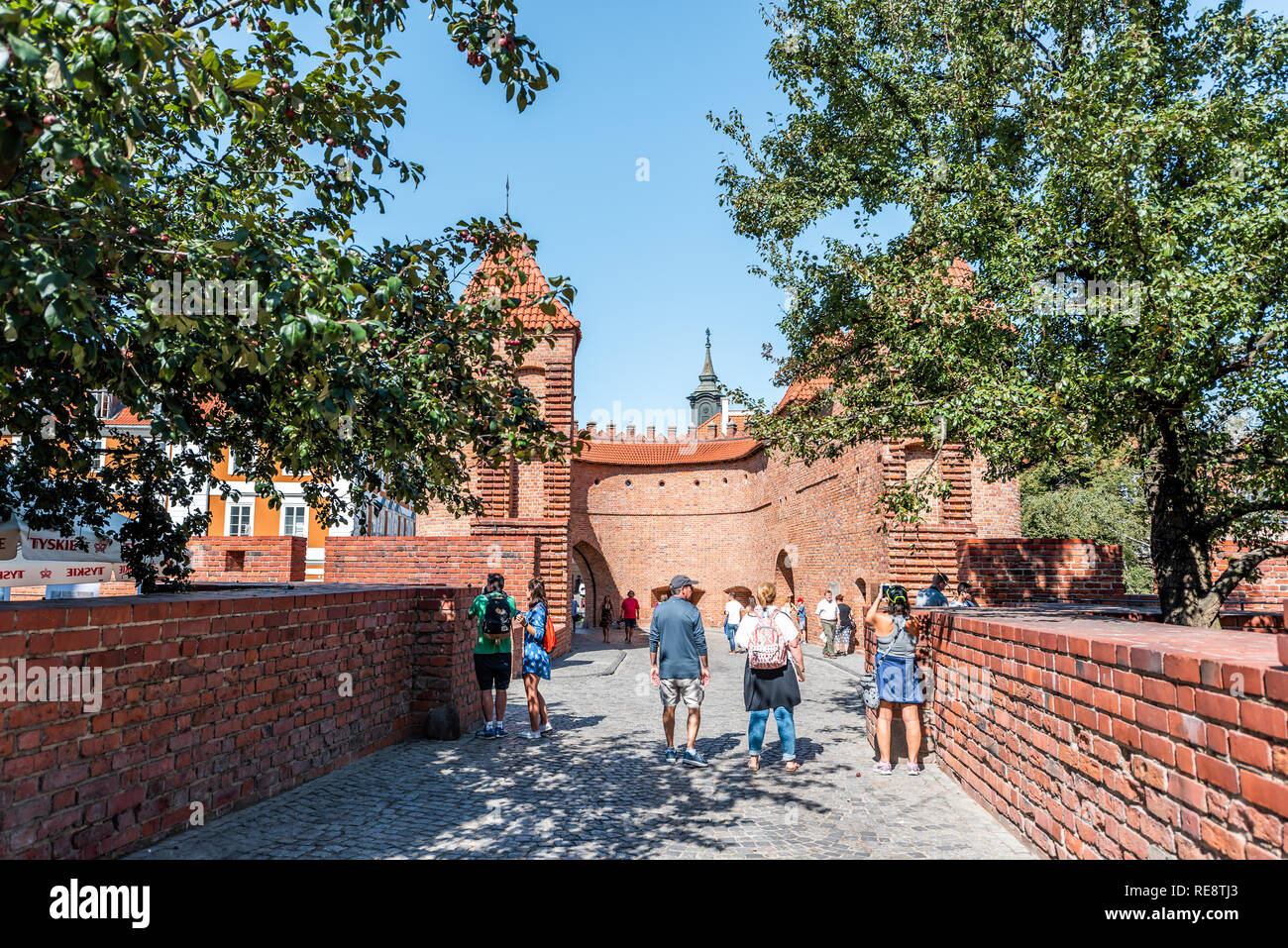 Warsaw, Poland - August 22, 2018: Famous old town historic street in capital city during sunny summer day and red orange brick wall fortress people wa Stock Photo