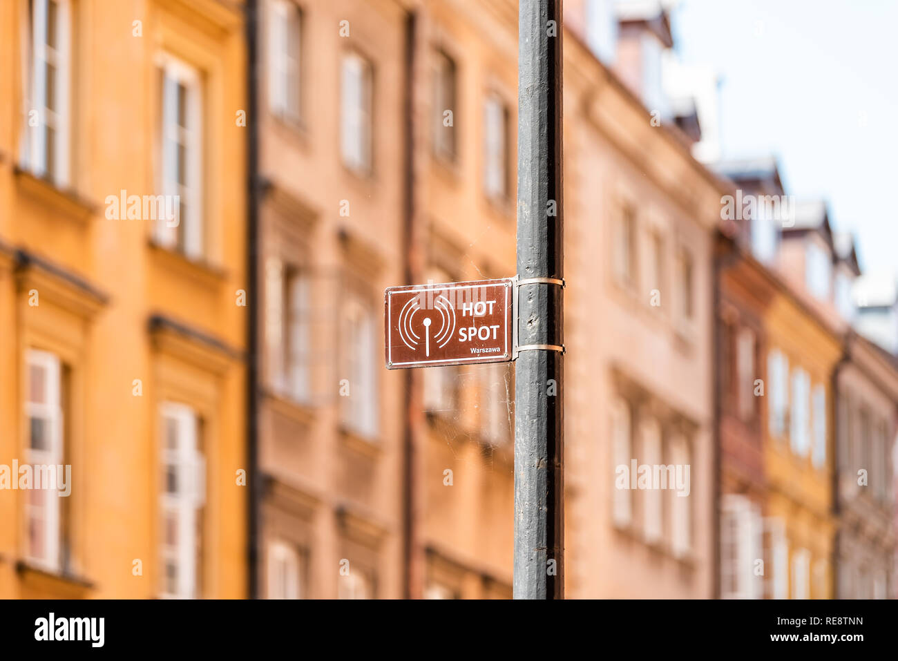 Warsaw, Poland Famous old town capital city architecture during sunny summer day cityscape background and closeup of sign for Warszawa Wifi Hot Spot o - Stock Image
