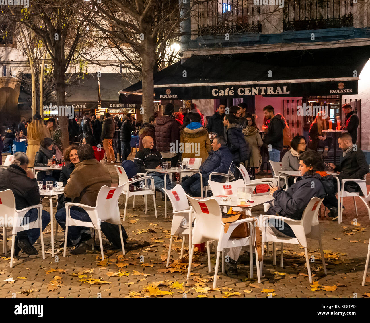 People at outside tables on a chilly winter night at a cafe in the Alameda de Hercules in Seville, Spain - Stock Image