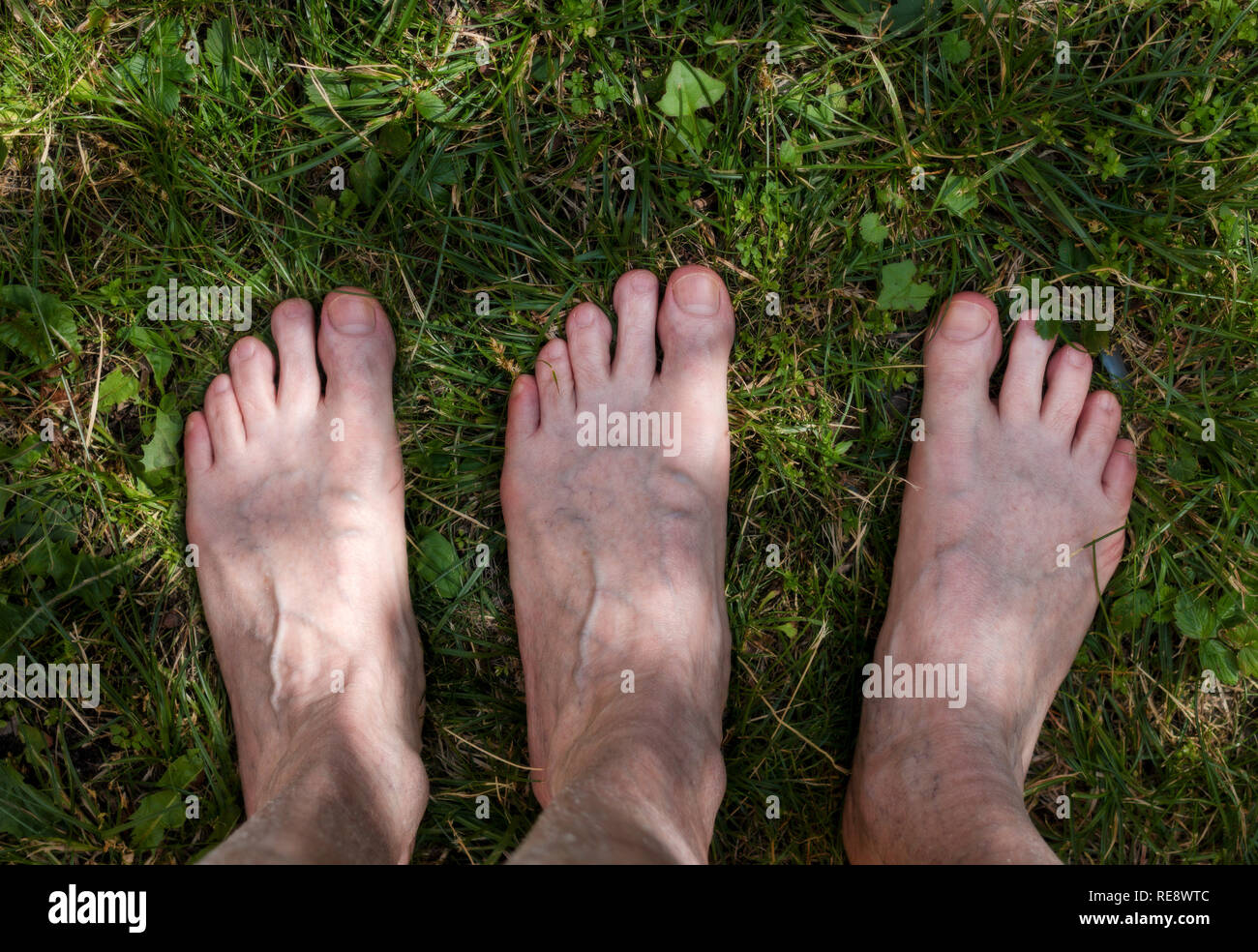 male adult funny feet on green grass - Stock Image