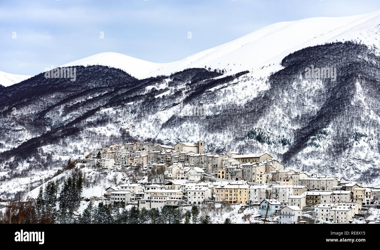 Aerial view of the beautiful snow-covered village of Opi with snow-capped mountains in the background. Stock Photo