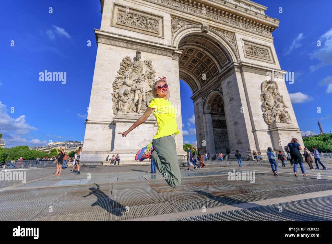 Woman with yellow vest jumping at Arch of triumph. Popular landmark in Paris, France. Concept of happiness for the triumph of people's protests. Gilets Jaunes are symbol of Parisian protest movement. - Stock Image