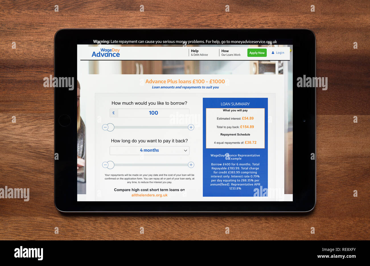 The website of Wage Day Advance is seen on an iPad tablet, which is resting on a wooden table (Editorial use only). - Stock Image