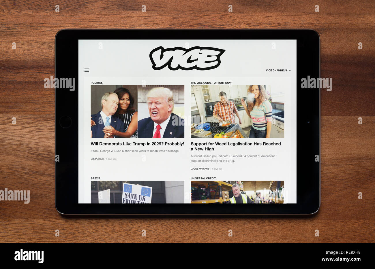The website of Vice is seen on an iPad tablet, which is resting on a wooden table (Editorial use only). - Stock Image