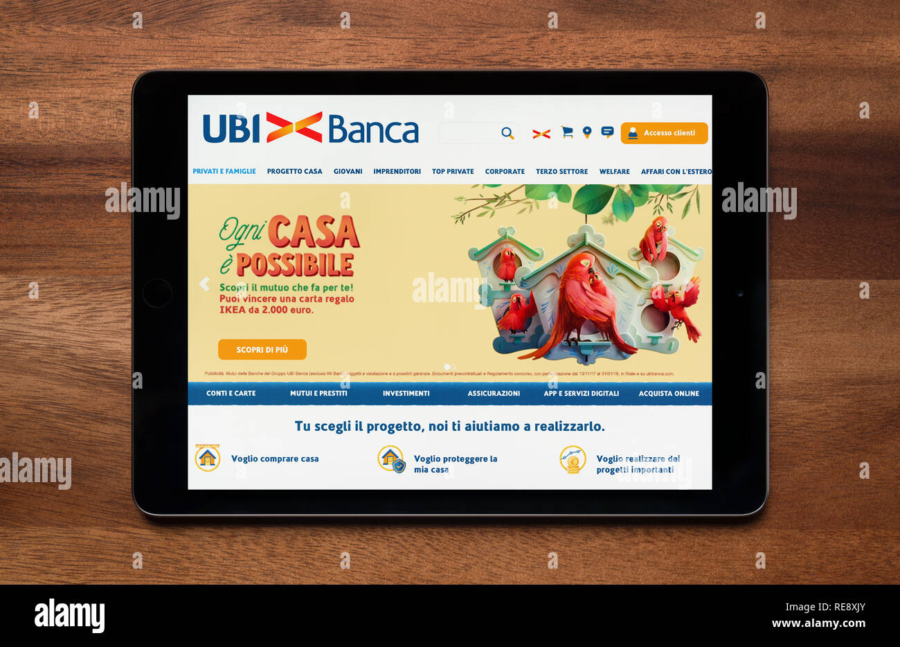 The website of Uni Banca is seen on an iPad tablet, which is resting on a wooden table (Editorial use only). - Stock Image