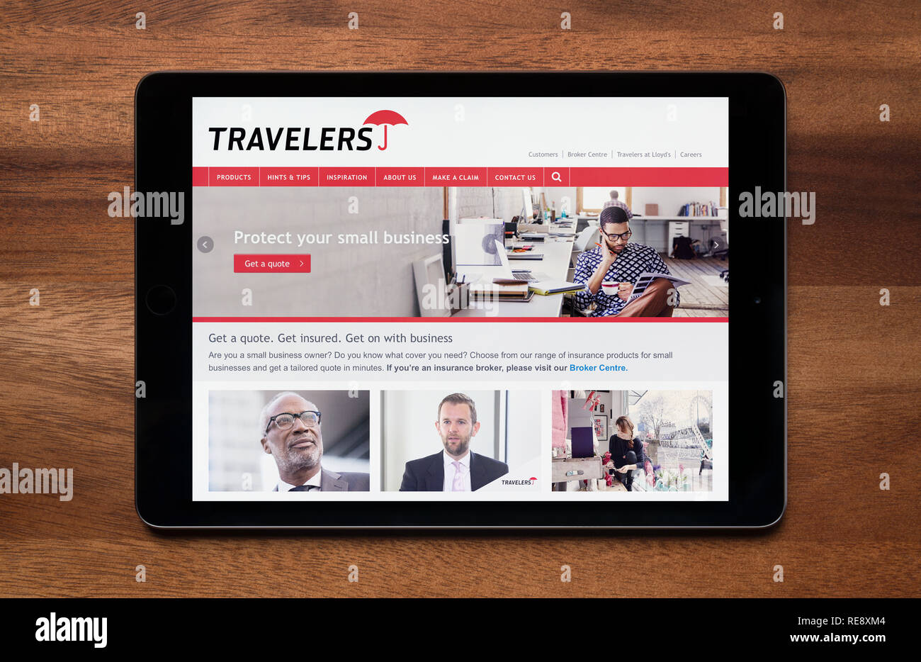 The website of Travelers Business Insurance is seen on an iPad tablet, which is resting on a wooden table (Editorial use only). - Stock Image