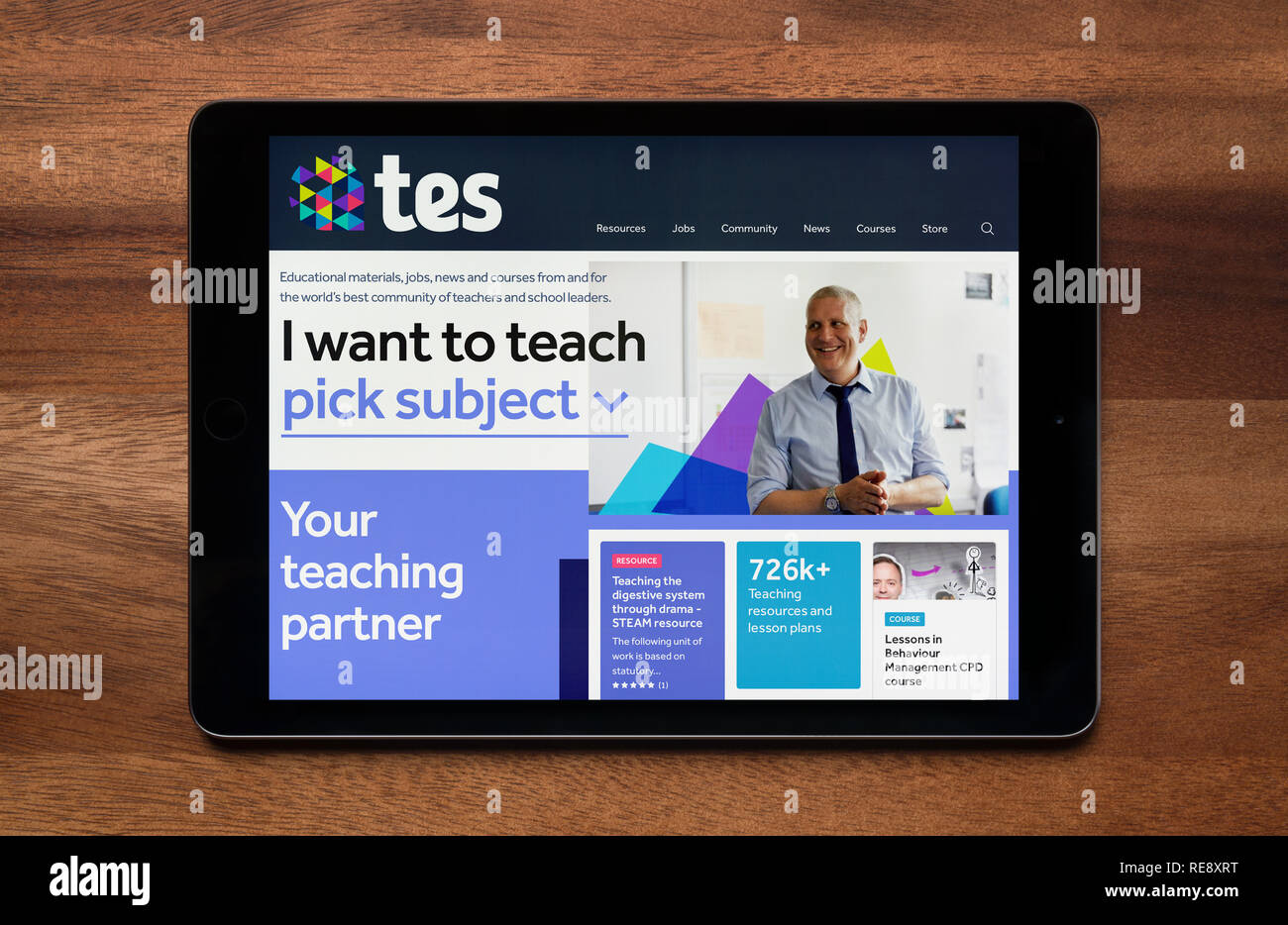 The website of TES (formerly Times Educational Supplement) is seen on an iPad tablet, which is resting on a wooden table (Editorial use only). - Stock Image