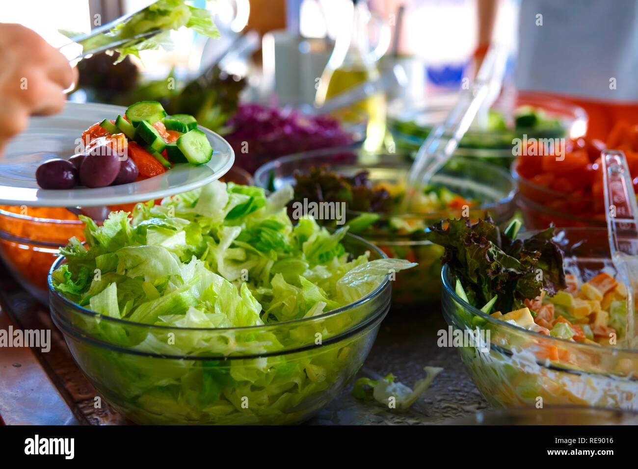 Salad buffet. The people themselves impose the desired treat. - Stock Image