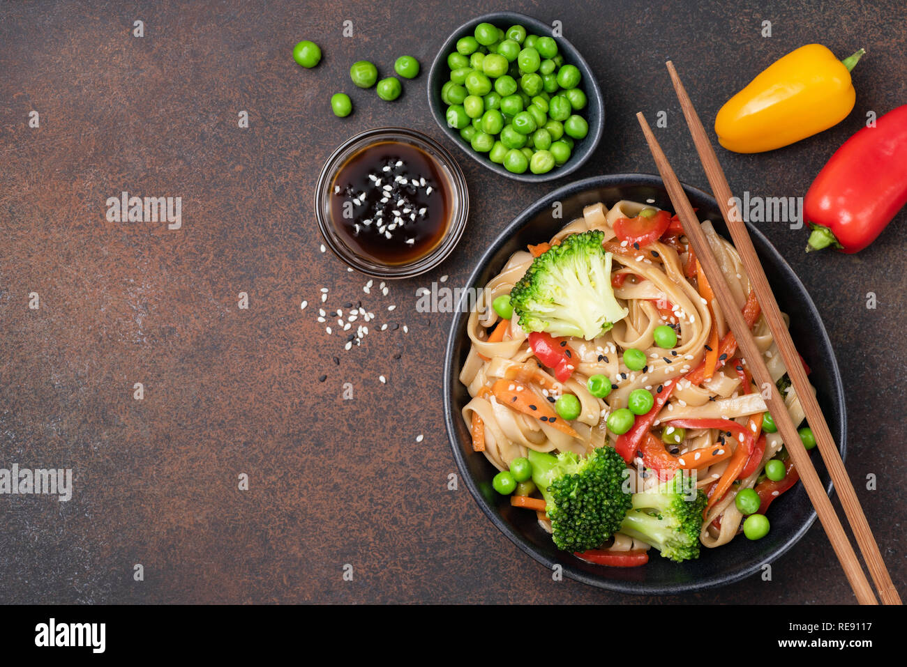 Noodles stir fry with vegetables. Udon noodles with broccoli, green pea, carrot, pepper and teriyaki sauce Stock Photo