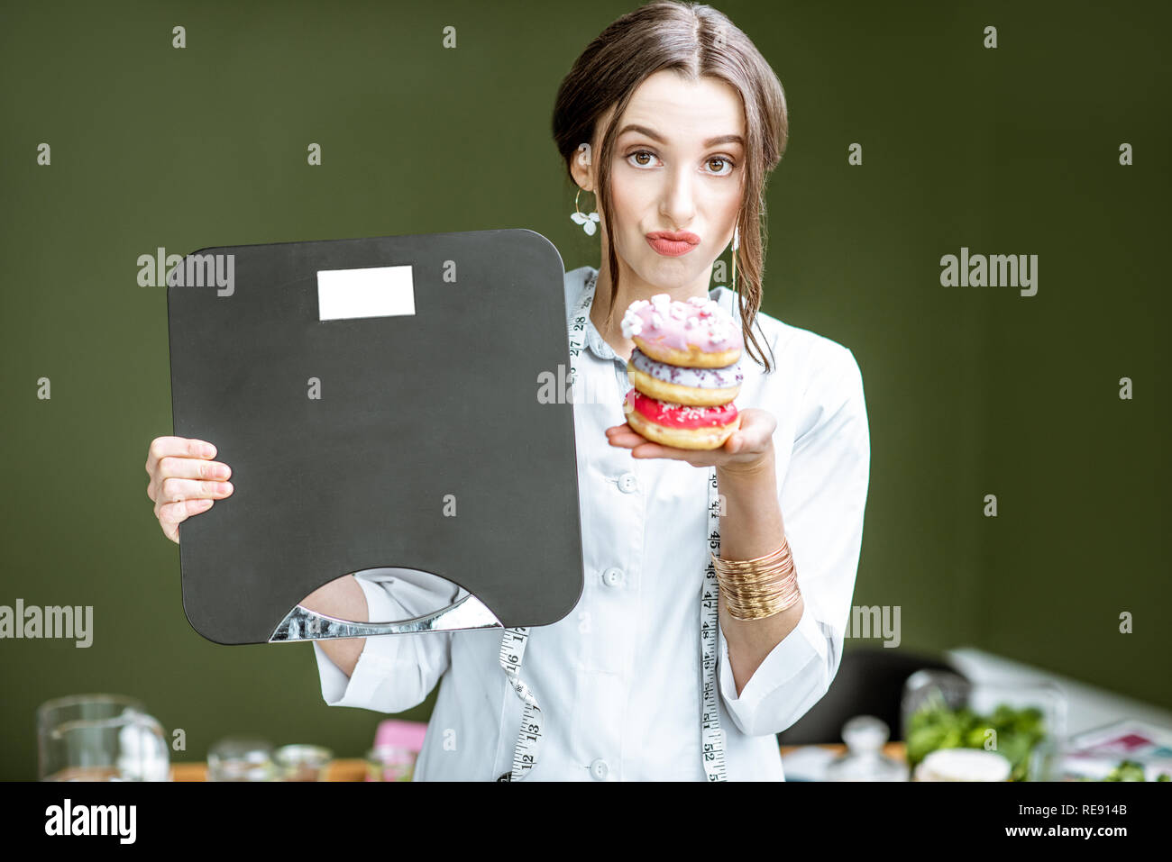 Portrait of a sad woman nutritionist in medical gown with donuts and weights on the green background. Unhealthy eating and adiposity concept - Stock Image