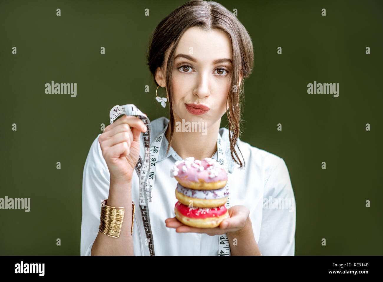 Portrait of a sad woman nutritionist in medical gown with donuts and tape measure on the green background. Unhealthy eating and adiposity concept - Stock Image