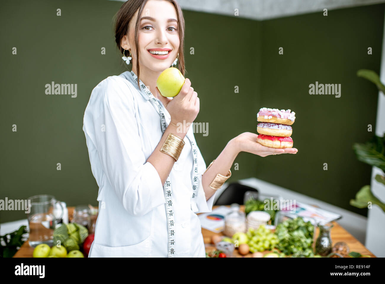 Young woman nutritionist looking on the apple choosing between healthy food and sweet dessert - Stock Photo