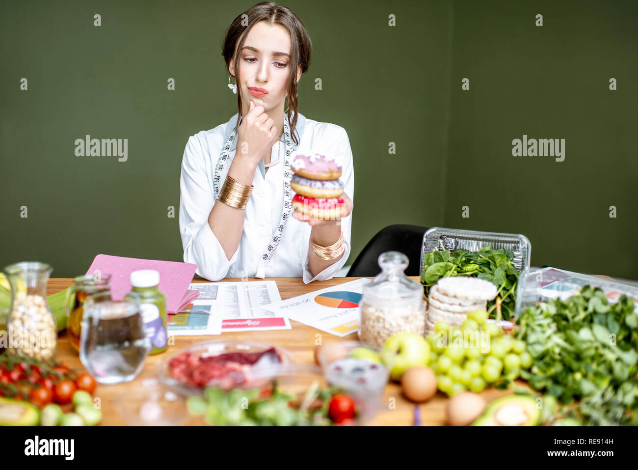 Portrait of a sad woman nutritionist holding sweet donuts sitting at the table full of healthy food on the green background - Stock Image
