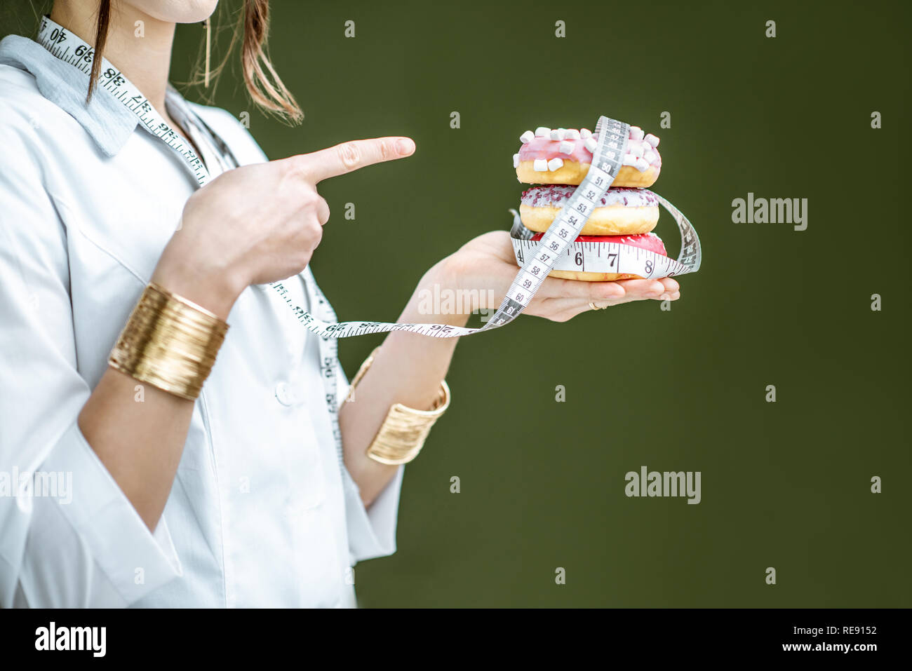 Woman showing on the sweet donuts on the green background. Unhealthy eating and adiposity concept - Stock Image