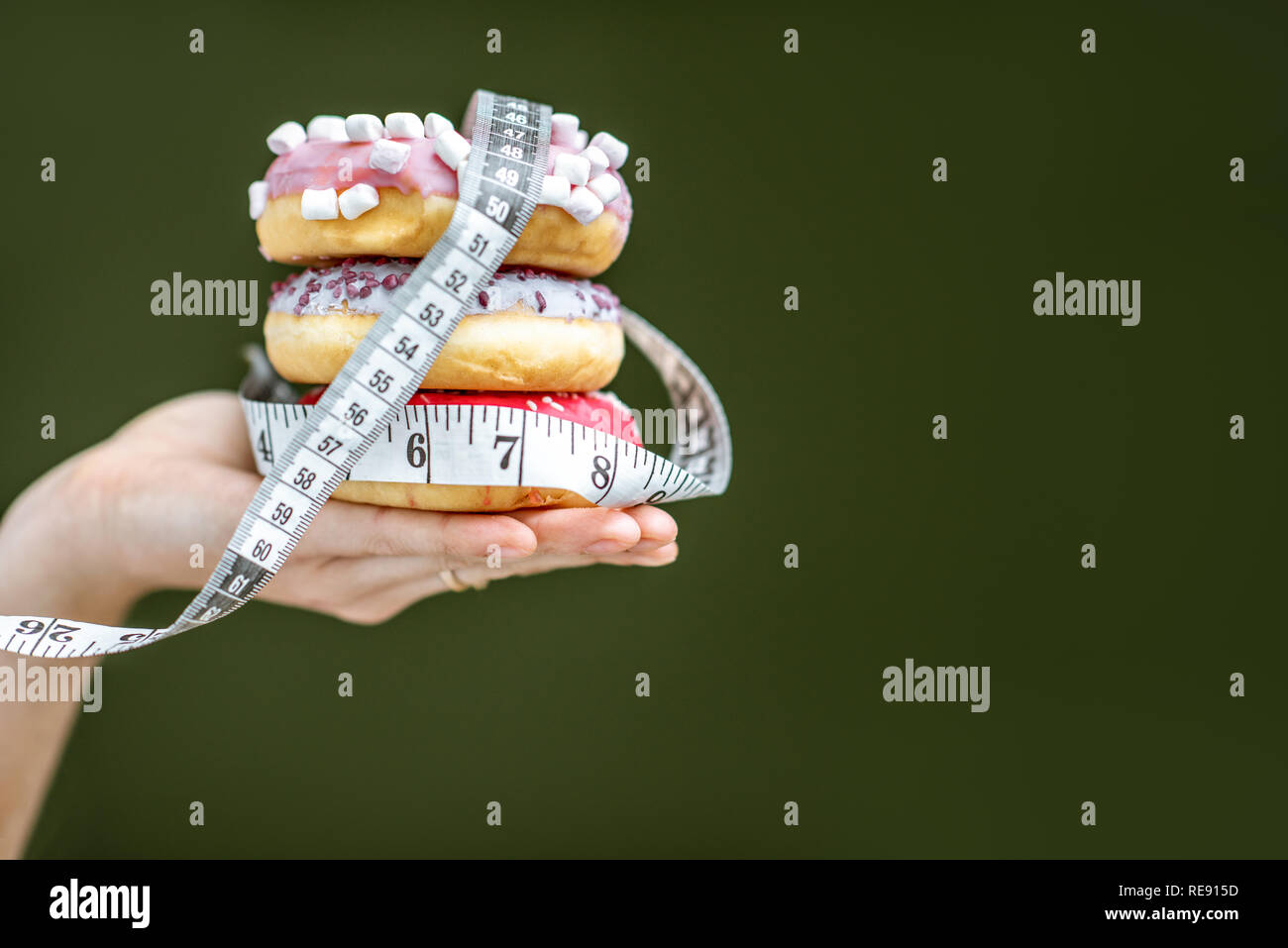 Three sweet donuts covered with measurement tape on the hand on the green background. Unhealthy eating and adiposity concept - Stock Image