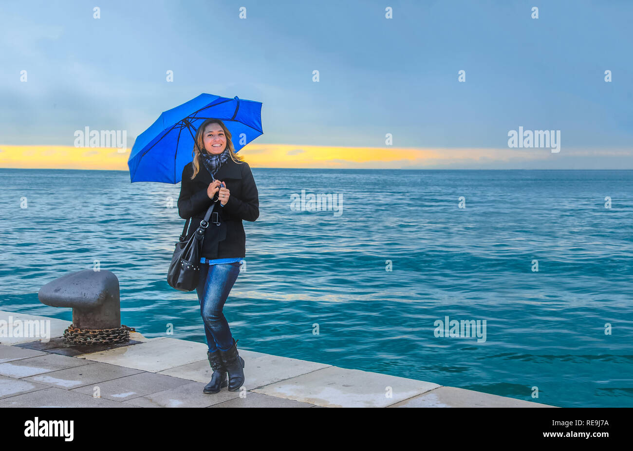 smiling woman with umbrella on stormy sea raining horizontal background  - Stock Image