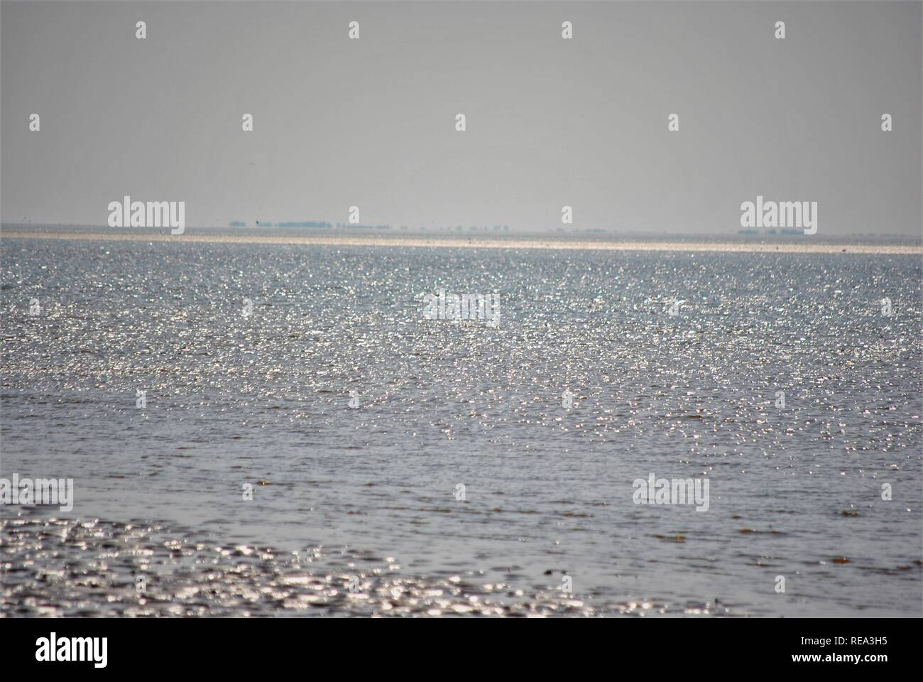 Sun sparkling  on the sea with coast in th distance of the coast in England - Stock Image