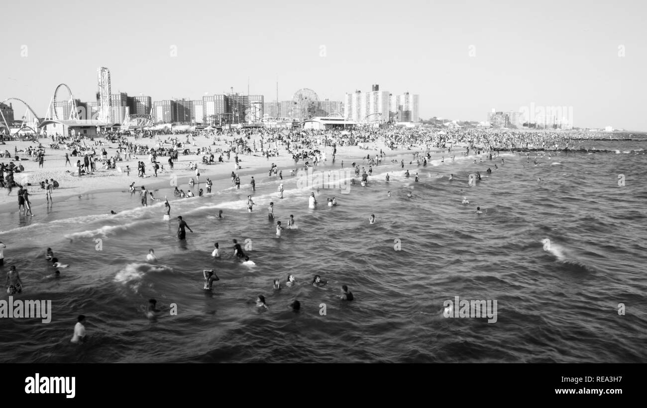 Beachgoers enjoy the ocean on Coney Island on a hot summer day - Stock Image
