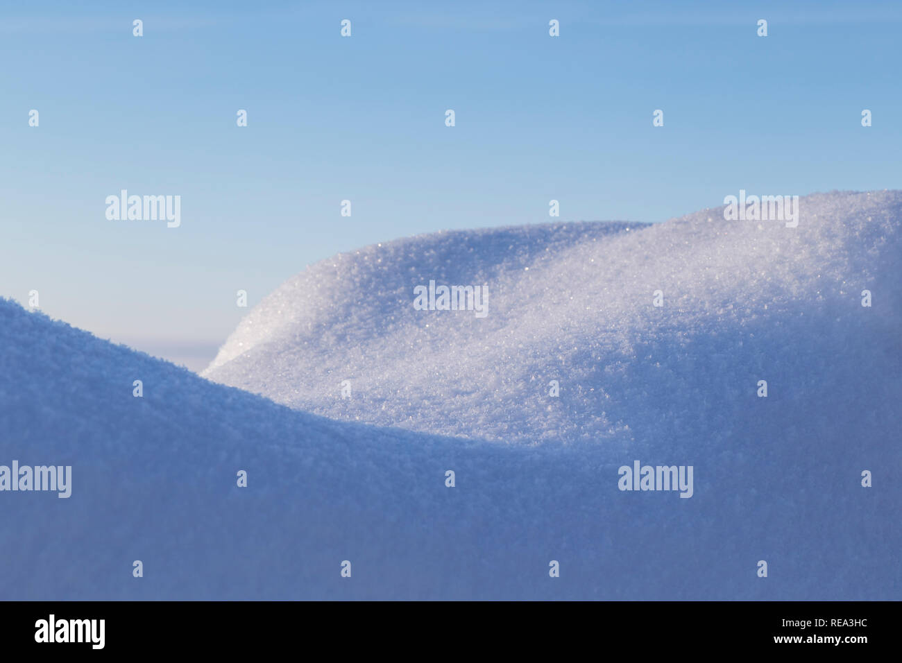 Close-up of fresh shiny snow on a snowdrift on a sunny day in the winter. Clear blue sky. - Stock Image