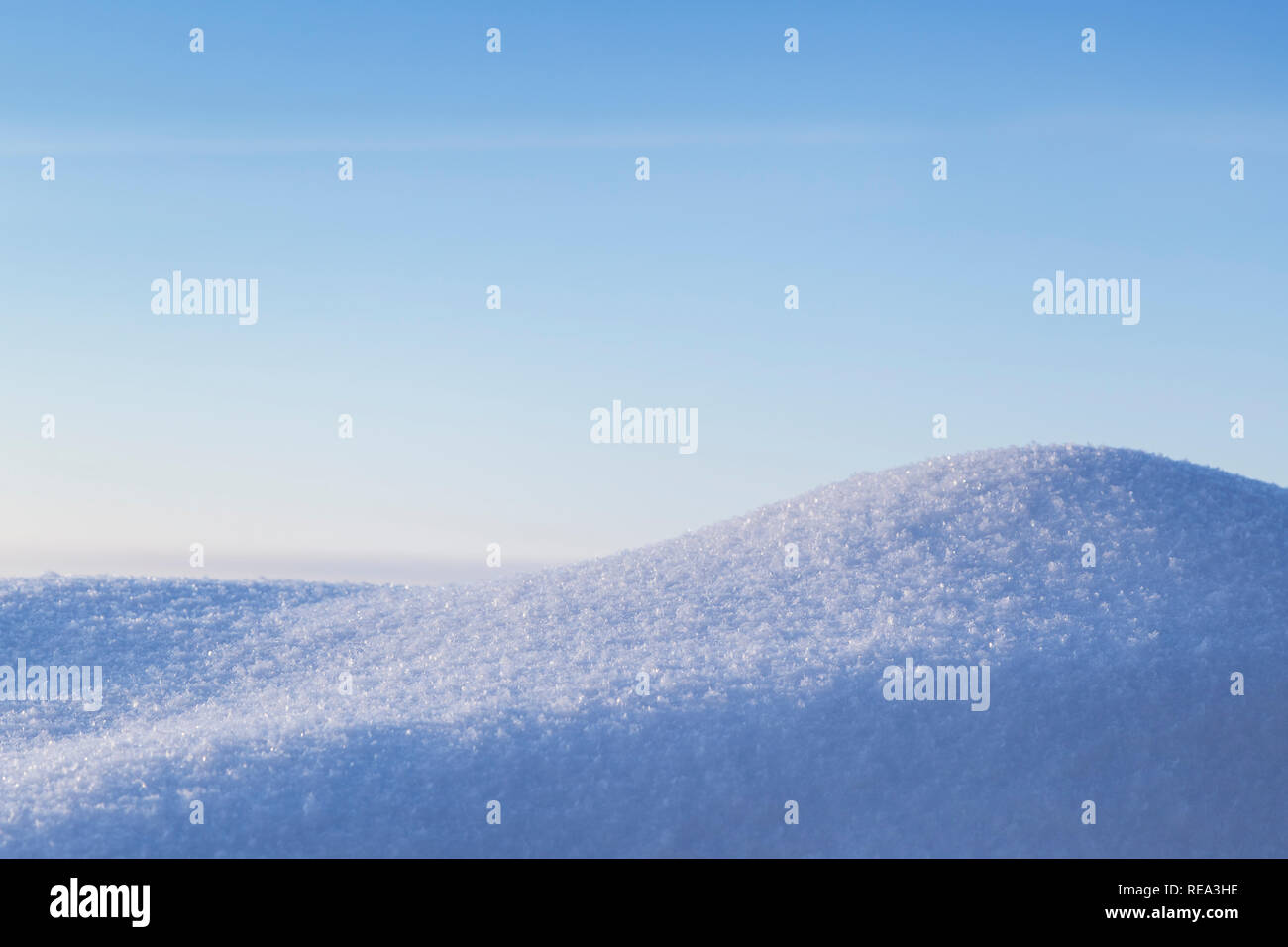 Close-up of fresh shiny snow on a snowdrift on a sunny day in the winter. Clear blue sky, copy space. - Stock Image