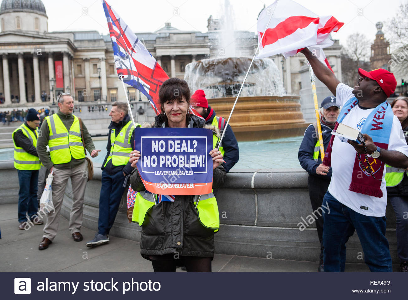 London, UK. 19 January 2019. Woman Yellow Vest protestor holds placard prior to start of march while bystander tries to catch flag. Graeme Barbour/Ala - Stock Image