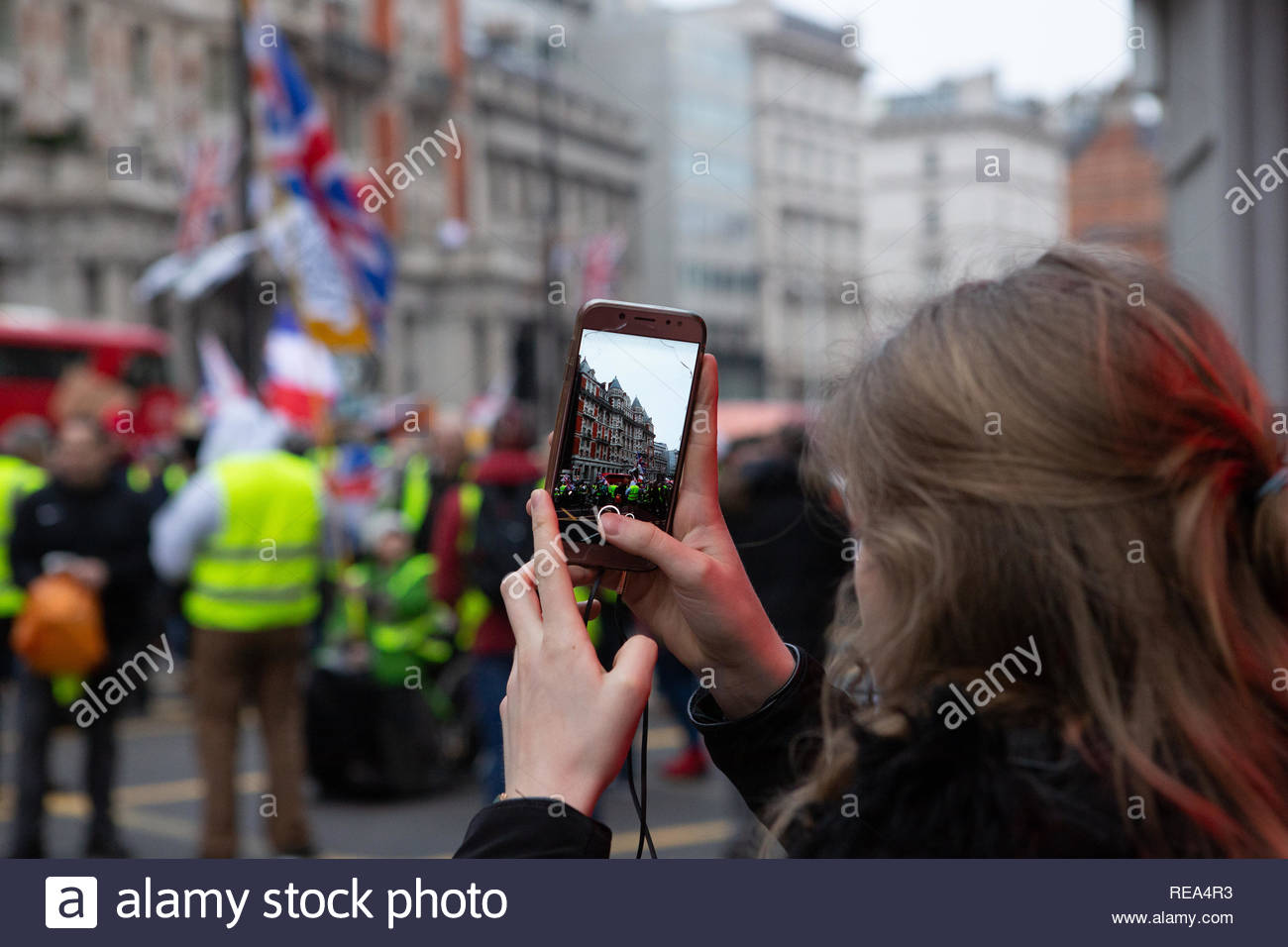 London, UK. 19 January 2019. Woman films Yellow Vest protest on her mobile phone. Graeme Barbour/Alamy - Stock Image