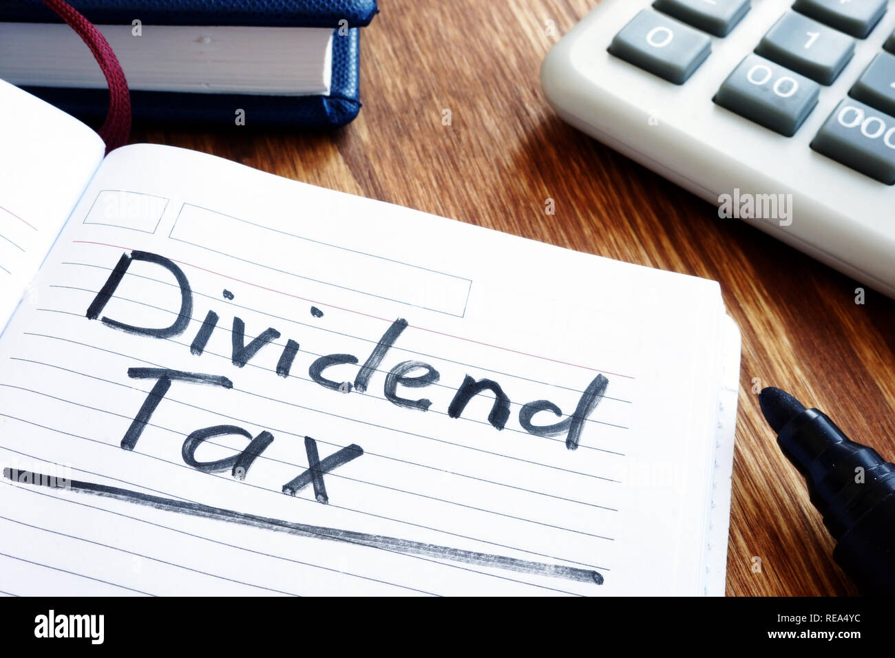 Dividend tax concept. Note pad and calculator. - Stock Image