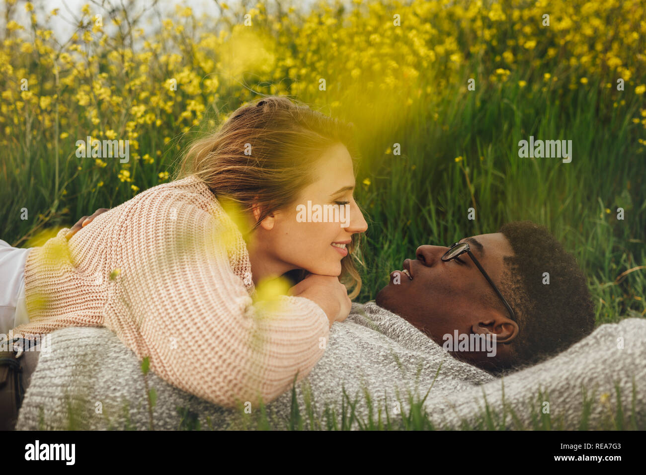 Young woman lying on her boyfriend outdoors. Young multi-ethnic couple lying on the grass in meadow and looking into each other's eyes. - Stock Image