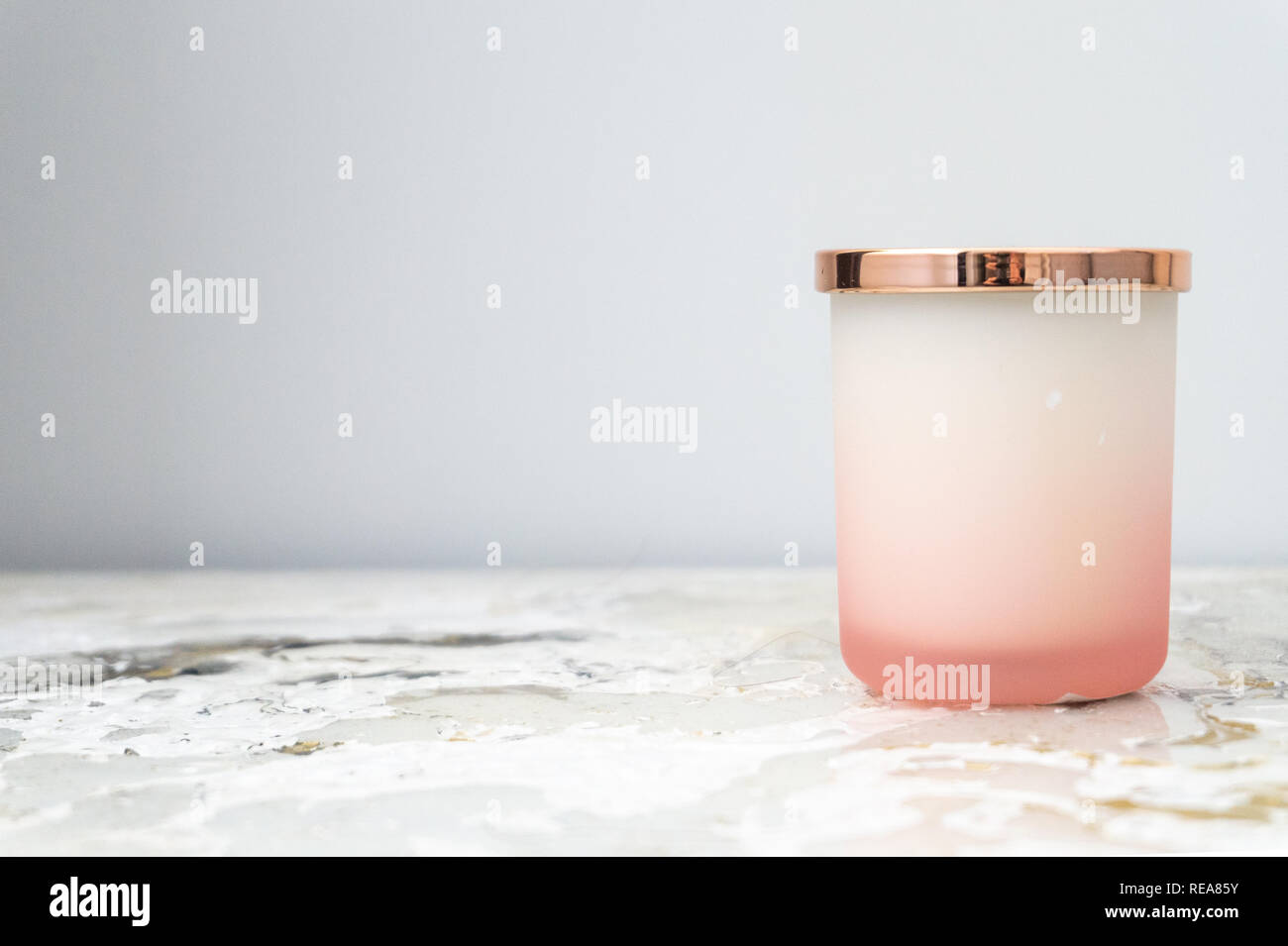 Rose pink and white ombre candle jar with a shiny gold lid, sitting on a bedside table (night stand). Candle is not lit. Daytime. - Stock Image