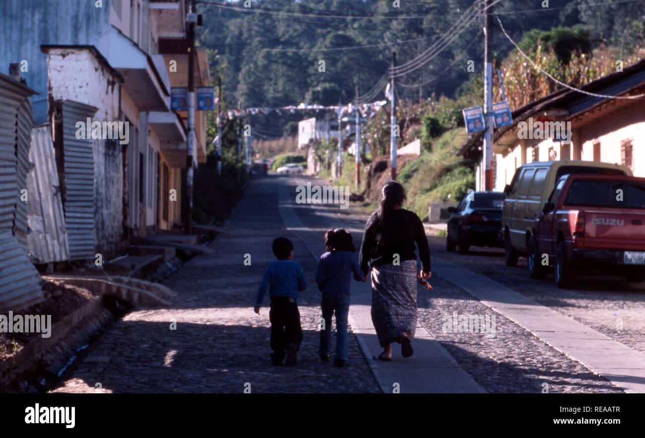 An indigenous Kiche Mayan woman walking home with her children, Momostenango Township, Guatemala. - Stock Image