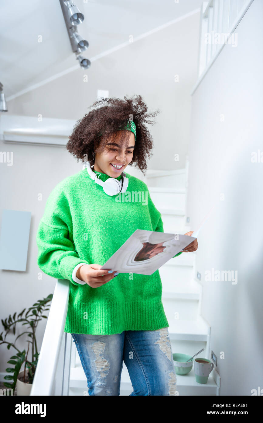 Curious young lady reading educative magazine on educational topic - Stock Image