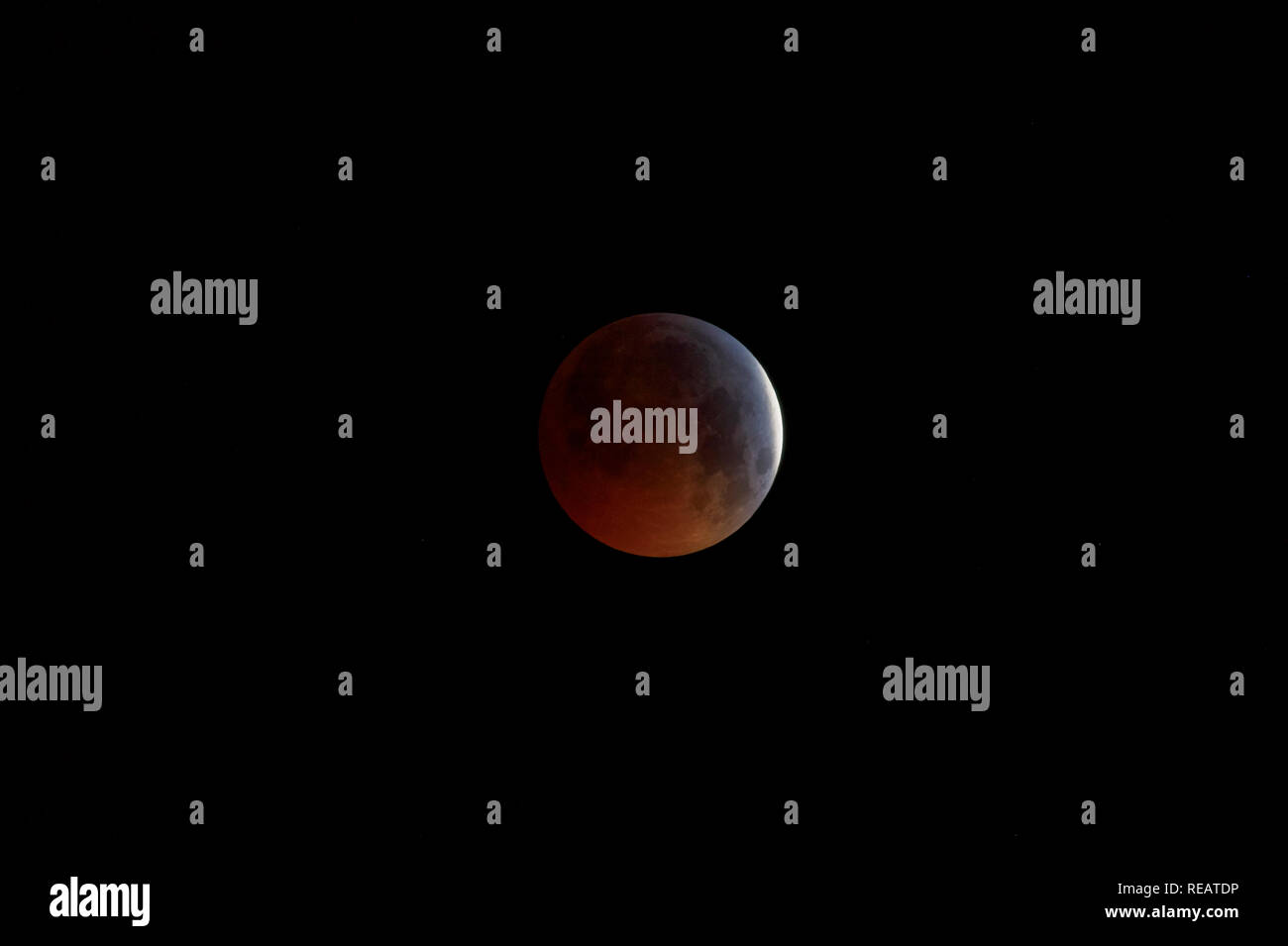 Woking, Surrey, England, UK, 21st January 2019.  The Super Blood Wolf Moon, the lunar eclipse of 21 January 2019, viewed from Woking, Surrey, south-east England, UK.  The shadow of the Earth partially covers the Moon shortly before totality of the eclipse. Credit: Graham Prentice/Alamy Live News. - Stock Image