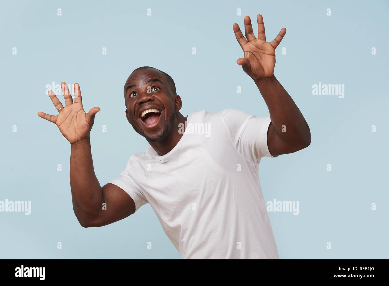 Handsome bold black man in white T-shirt is smiling, against pale blue background. ?razy eyes, eyebrows raised. Wow gesture. Grimacing. - Stock Image