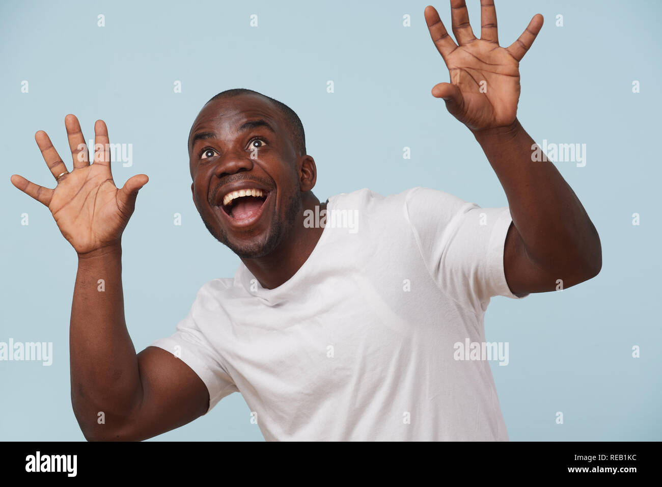 Handsome bold black man in white T-shirt is smiling, against pale blue background. ?razy eyes, eyebrows raised. Wow gesture. Grimacing. Close up. - Stock Image