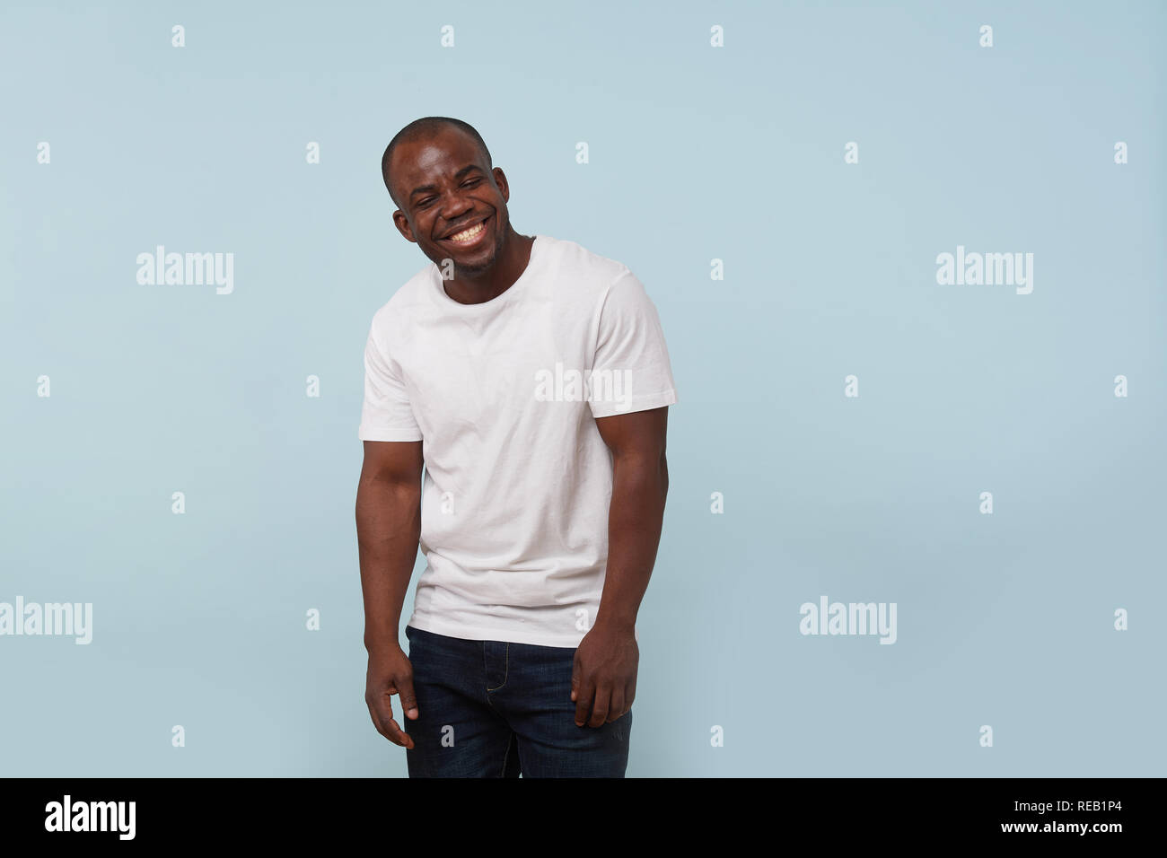 Handsome bold black man in white T-shirt grimacing against pale blue background. Relaxed, arms down, giggling, eyes closed. Laughing at something funn - Stock Image