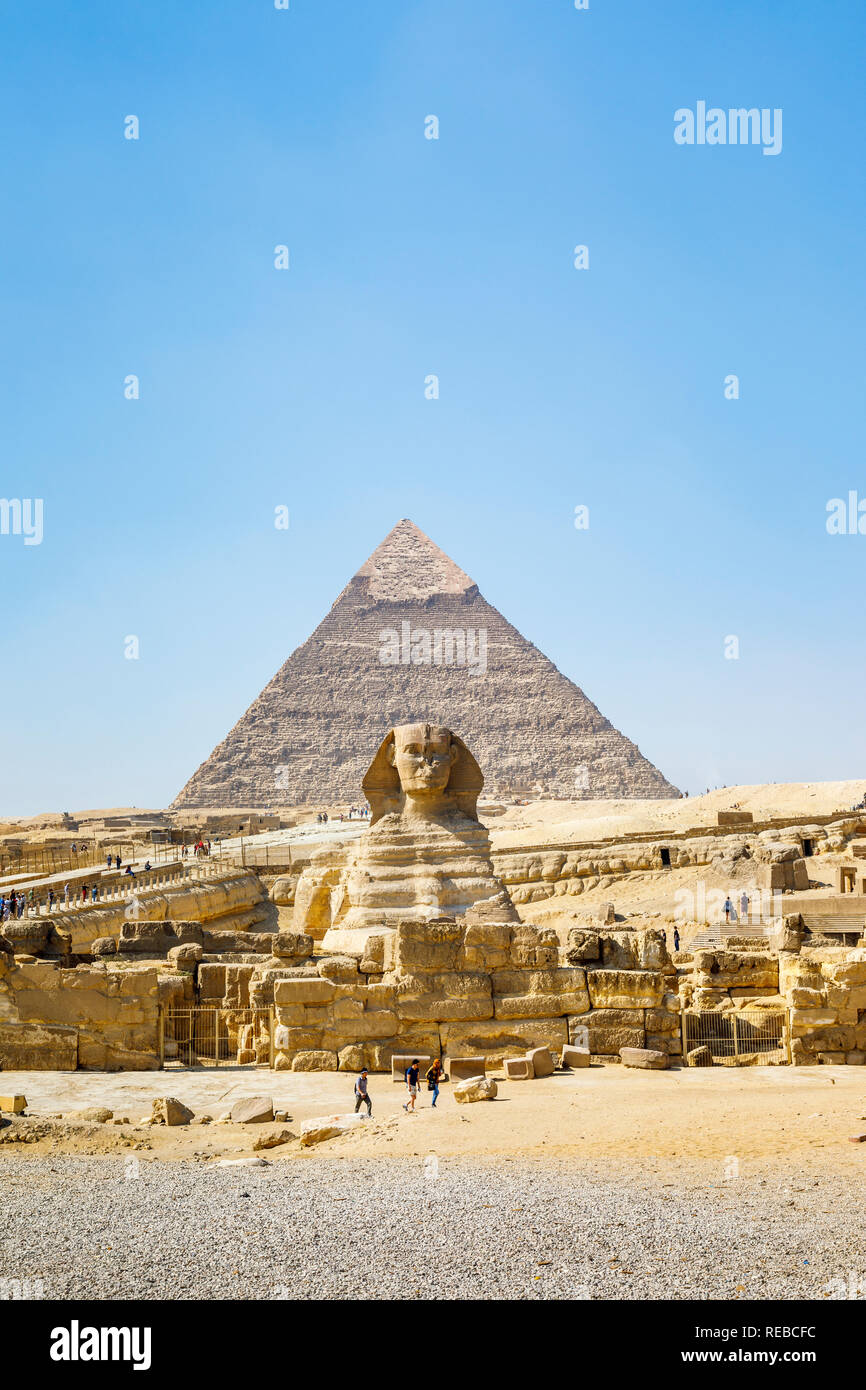 The iconic monumental sculpture, the Great Sphinx of Giza with the Pyramid of Khafre, one of the Great Pyramids, behind, Giza Plateau, Cairo, Egypt Stock Photo