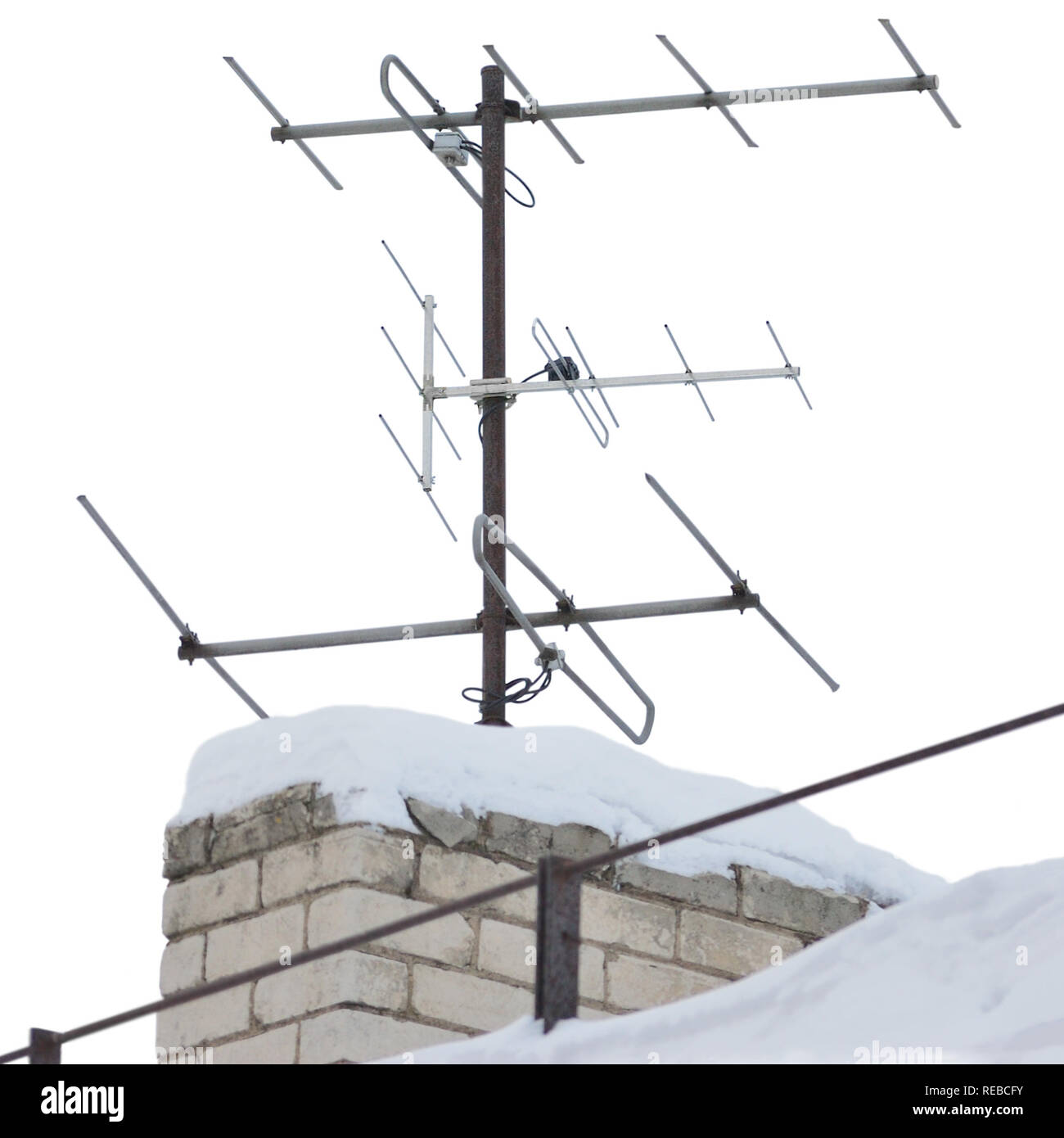 TV and communication aerials on snowy roof of residential house, multiple isolated dvb-t antennas winter scene, large detailed vertical closeup, rusty Stock Photo
