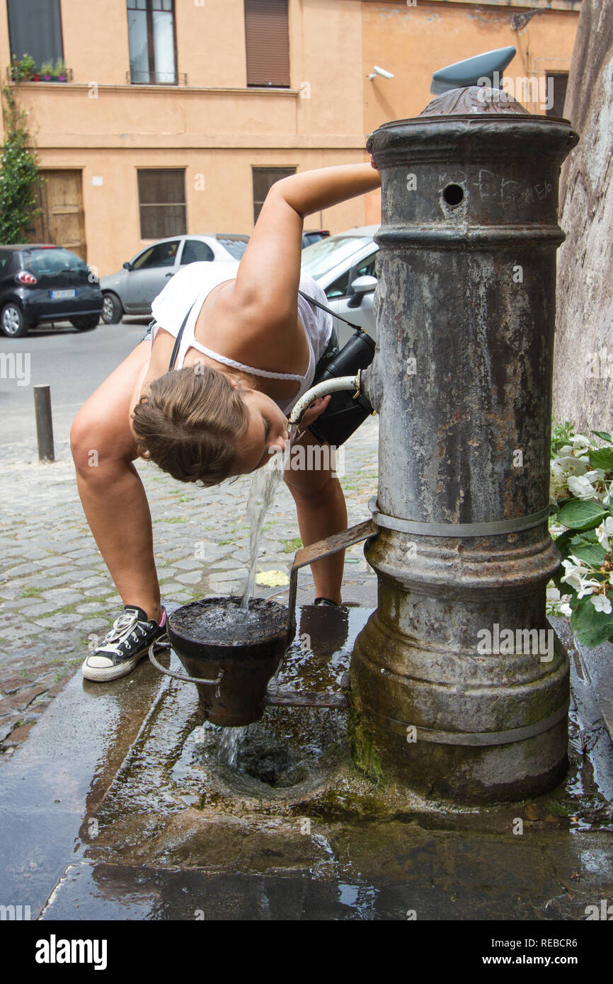 A young female tourist stops at an ancient roman water fountain for refreshment during a walking tour. Rome, Italy - Stock Image