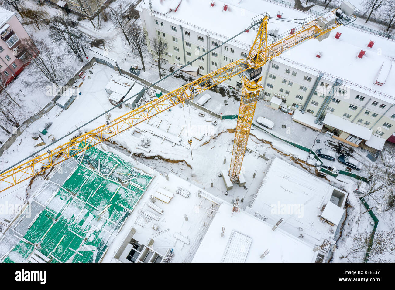 aerial top view of tall tower crane working at construction site in winter. drone photography - Stock Image