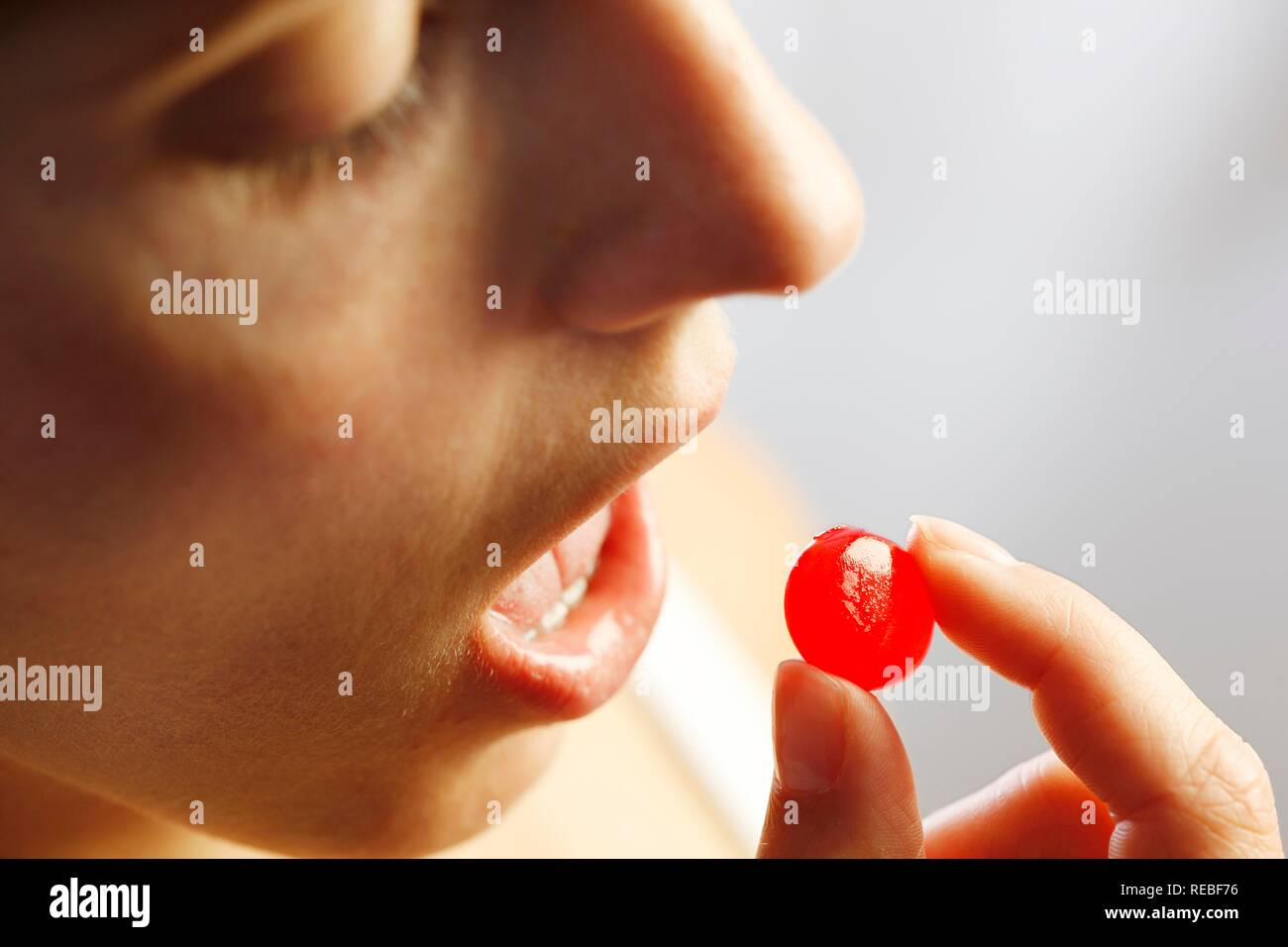 Young woman taking a throat lozenge - Stock Image