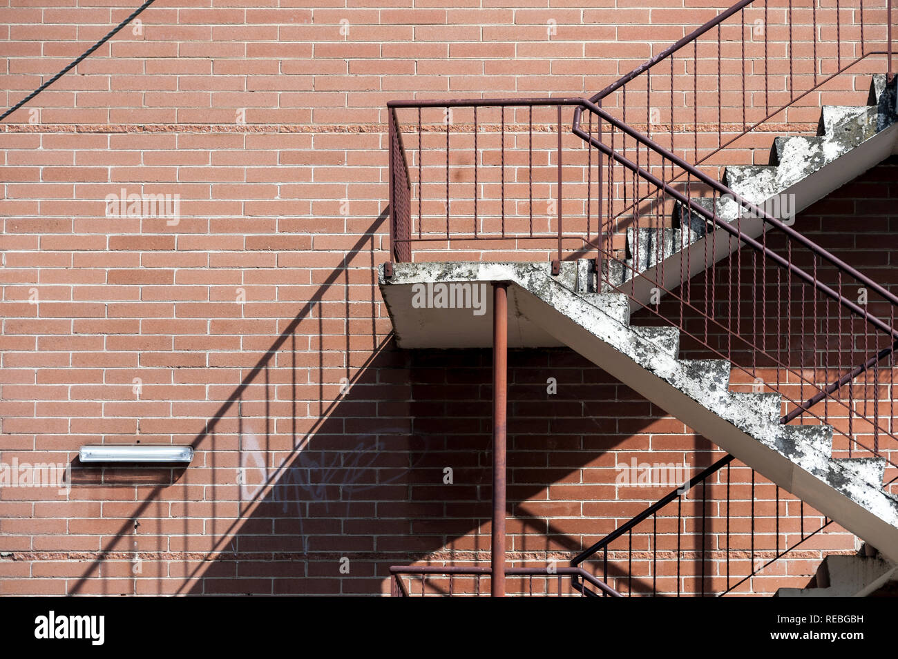 Concrete stairs with red metal railings against a red brick wall creating a strong diagonal shadow pattern Stock Photo