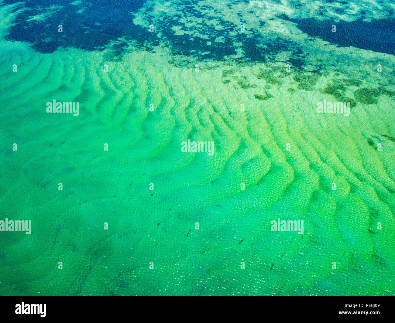 Incredible patterns and textures left by the sand with turquoise water glistening above. Pumicestone Passage, Sunshine Coast, QLD, Australia. - Stock Image