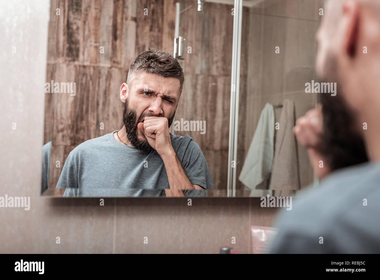 Businessman yawning while feeling sleepy in the morning - Stock Image